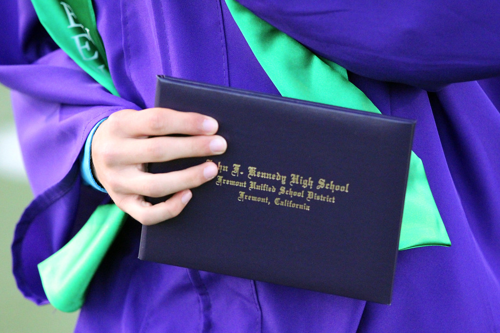 . A Kennedy High School graduate holds his diploma as he walks back to his seat during the school\'s commencement ceremony in Fremont, Calif., on Wednesday, June 19, 2013. (Anda Chu/Bay Area News Group)