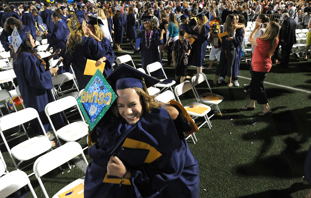 . Alhambra High School graduate Madison McGrath, right, gives a hug to a classmate after their commencement ceremony in Martinez, Calif., on Friday, June 7, 2013. The graduation also featured a song by graduates Halia Roth, Ericka March, Connor Francis, and Harrison Flynn. Class president Christain Bumala and Salutatorian Thomas Schwemberger also gave speeches. (Doug Duran/Bay Area News Group)