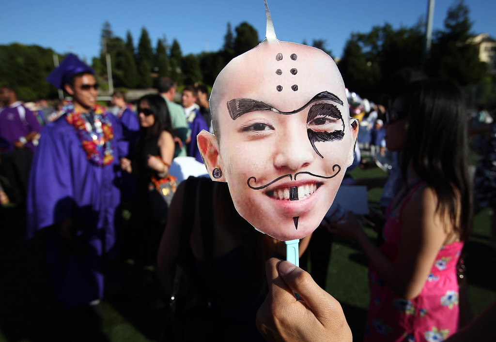 . Marcus Biray, of Berkeley, right, holds a cutout of his friend and graduate Jonathan Tran, to the left, backround, during commencement ceremonies at Piedmont High School in Piedmont, Calif., on Thursday, June 13, 2013.  (Jane Tyska/Bay Area News Group)