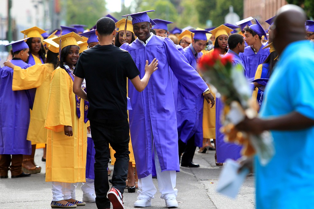 . Michael Ochoa, 18, center, is greeted by classmate Jamii Young, 18, center left, as they line up to enter graduation ceremonies at the Paramount Theatre in Oakland, Calif., on Tuesday, June 11,  2013. The school graduated 351 students in the class of 2013. (Jane Tyska/Bay Area News Group)
