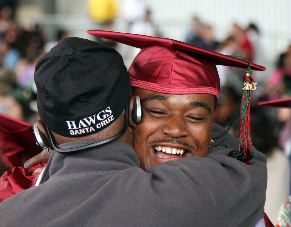 . Onaje Pree, right, gets a congratulatory hug from his grandfather, James Porter, at the the conclusion of the graduation ceremonies for Mt. Diablo High Schoo held at the Sleep Train Pavilion in Concord, Calif., on Sunday, June 9, 2013. It is the 100th anniversary of the school,  which graduated three students in 1913 and 300 on Sunday. (Jim Stevens/Bay Area News Group)