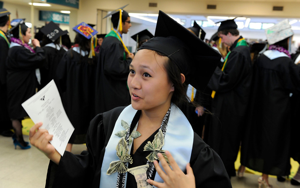 . Senior Philline Miguel, 17, of Antioch fans herself in the cafeteria while she waits for the Dozier-Libbey Medical High School 2013 Commencement Ceremony to begin at Deer Valley High School in Antioch, Calif., on Wednesday, June 5, 2013. (Susan Tripp Pollard/Bay Area News Group)