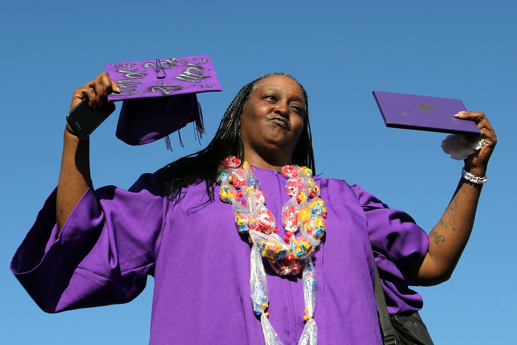 . Wolanda Christopher wears the cap and gown of her deceased son Olajuwon Clayborn as she holds up his diploma in a tribute to his memory during the Castlemont High School graduation ceremony of the Class of 2013 in Oakland, Calif., on Friday, June 14, 2013. Clayborn was killed in East Oakland on May 5, 2013.  (Ray Chavez /Bay Area News Group)