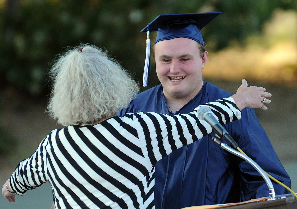 . Graduate Dylan White, gets a hug from Cathy Riggs from the Martinez Arts Association after getting a scholarship during the Vicente-Martinez High School and Briones School commencement ceremony in Martinez, Calif., on Wednesday, June 5, 2013. The graduation also featured class speeches by graduates Maalec Thomas and Serenity McGill, a performance by graduate Nicholas Napolitano and scholarship presentations by Martinez organizations. (Doug Duran/Bay Area News Group)