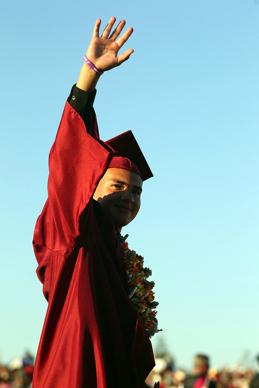. Cristian Ortiz, 19, waves to family and friends during the Liberty High School Class of 2013 commencement ceremony on the school\'s Ohmstede Field in Brentwood, Calif., on Friday, June 7, 2013. (Anda Chu/Bay Area News Group)