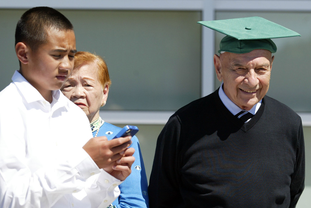 . Mike Rabim, right, wears his grandson Justin Pagila\'s cap  as his younger brother Jared, 13, uses his smartphone following his commencement ceremony of the Class of 2013 at De La Salle High School in Concord, Calif., on Sunday, May 19, 2013. (Ray Chavez/Bay Area News Group)