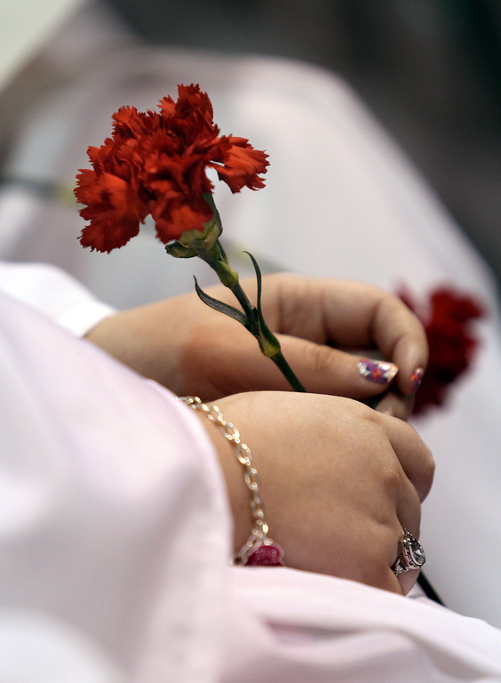 . A Carondelet High School graduate of the Class of 2013 holds a carnation during their commencement ceremony at Carondelet High School in Concord, Calif., on Sunday, May 19, 2013. (Ray Chavez/Bay Area News Group)