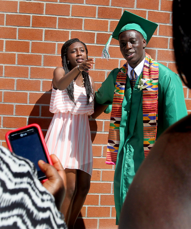 . De La Salle graduate Kofi Poku, right, and his sister Akua,15, get ready to have their picture made by family members and friends following the commencement ceremony of the Class of 2013 at De La Salle High School, in Concord, Calif., on Sunday, May 19, 2013. (Ray Chavez/Bay Area News Group)