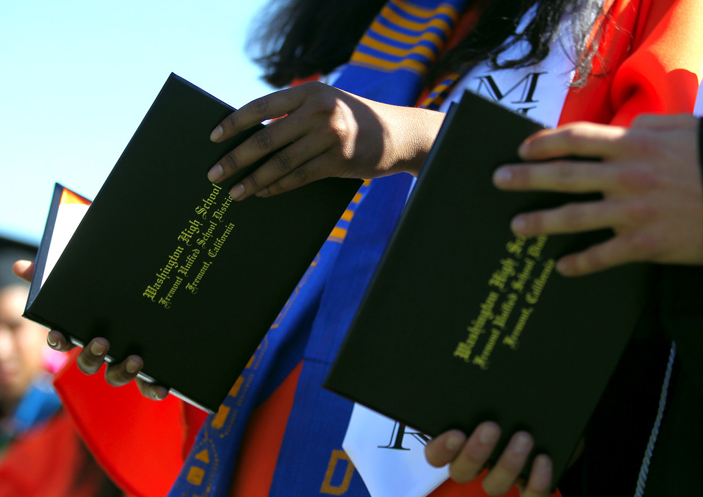 . Washington High School Class of 2013 graduates look over their diplomas during their commencement ceremony in Fremont, Calif., on Wednesday, June 19, 2013. (Anda Chu/Bay Area News Group)