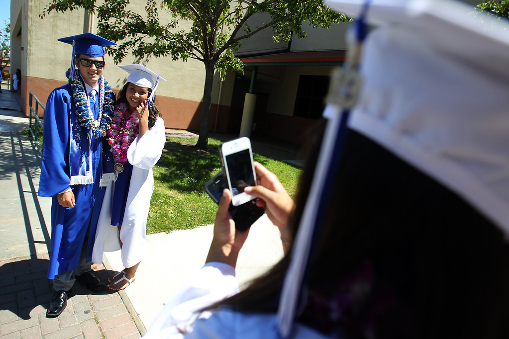 . Devin Martinez, 18, and Katrina Vu, 18, from left, Irvington High School graduates pose for a photograph taken by fellow graduate Jamie Ascanio, 17, before their commencement ceremony in Fremont, Calif., on Thursday, June 20, 2013. (Anda Chu/Bay Area News Group)