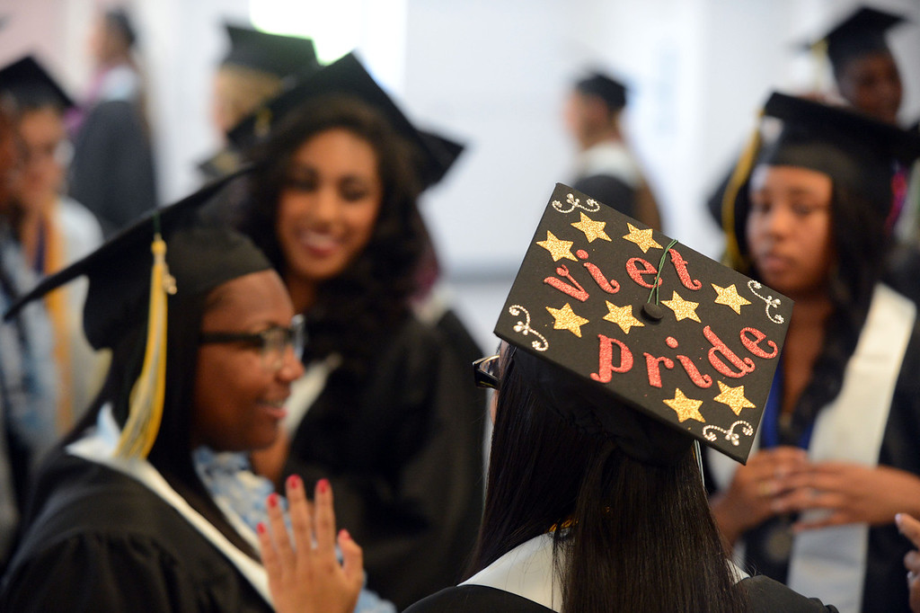 . Senior Theresa Pham, 18, of Antioch shares her Vietnamese pride as she gathers with friends in the cafeteria before the Dozier-Libbey Medical High School 2013 Commencement Ceremony held at Deer Valley High School in Antioch, Calif., on Wednesday, June 5, 2013. (Susan Tripp Pollard/Bay Area News Group)