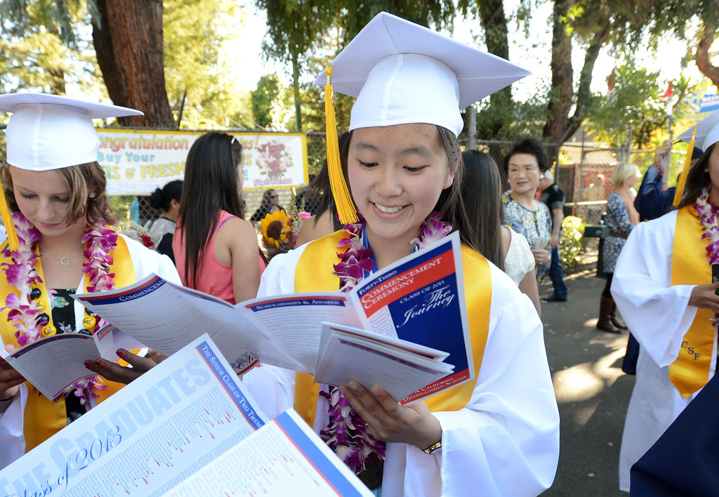 . Dublin High valedictorian Malina Jiang, looks through the commencement program before the start of their graduation ceremony held at the Alameda County Fairgrounds in Pleasanton, Calif., on Thursday, June 13, 2013. Jiang will be attending Stanford University in the fall. (Doug Duran/Bay Area News Group)
