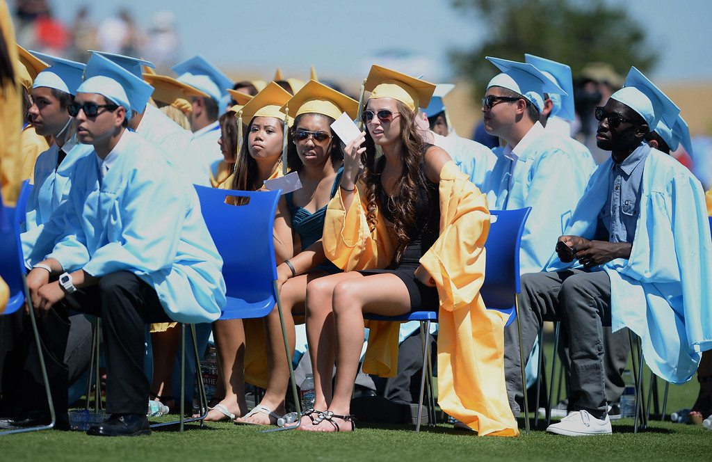 . Lexis Campberll, center right, and Erin Asher, center left, try to stay cool during the Heritage High School graduation ceremony held at Patriot Stadium on the campus of Heritage High School in Brentwood, Calif., on Saturday, June 8, 2013. (Dan Honda/Bay Area News Group)