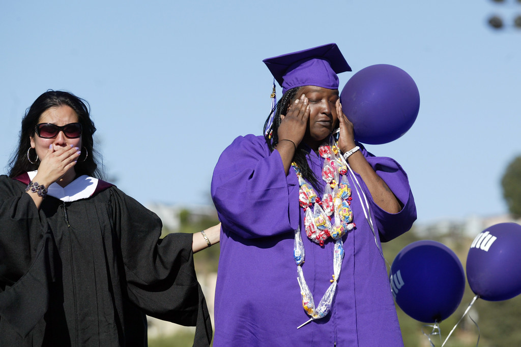 . Assistant Principal Christina Villareal, left, and Wolanda Christopher, mother of deceased senior Olajuwon Clayborn, cries during a tribute in his honor during the Castlemont High School graduation ceremony of the Class of 2013  at the school\'s football field in Oakland, Calif., on Friday, June 14, 2013.  Clayborn was killed in East Oakland on May 5, 2013.  (Ray Chavez / Bay Area News Group)