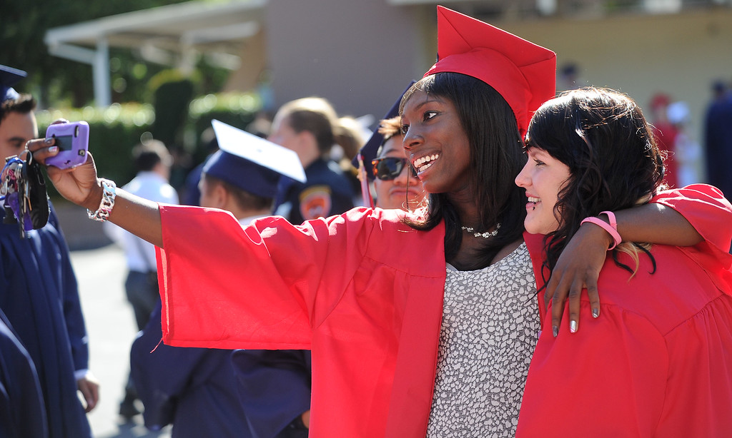 . Dublin High graduate Myiesha Simmons, left, takes a photo with classmate Meg Mannering, before the start of their Commencement Ceremony held at the Alameda County Fairgrounds in Pleasanton, Calif., on Thursday, June 13, 2013. (Doug Duran/Bay Area News Group)
