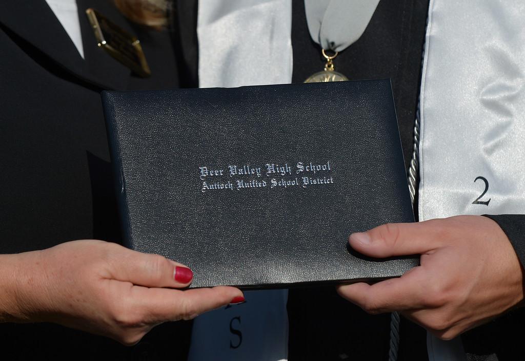 . Antioch Unified School District board member Joy Motts hands a diploma cover to valedictorian Alvin Vuong during graduation ceremonies at Deer Valley High School in Antioch, Calif., on Thursday, June 6, 2013. (Jose Carlos Fajardo/Bay Area News Group)