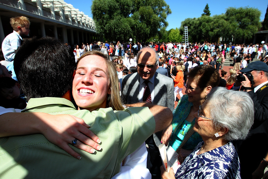 . Joe Fenech, left, gives a congratulatory hug to his cousin and graduate Kristen Byron after the commencement ceremony of Carondelet High School Class of 2013 at Carondelet High School in Concord, Calif., on Sunday, May 19, 2013. Byron will pursue a major in Biology at Cal Poly.  (Ray Chavez/Bay Area News Group)