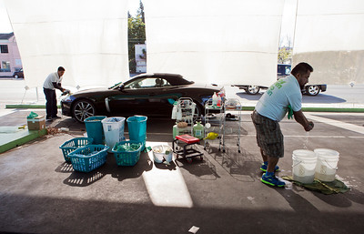 In the foreground right, Mario Altimaro wets a microfiber cloth with water from the buckets at EcoGreen Auto Clean, in Redwood City, Calif., on Friday, January 31, 2014.  The two buckets are basically all the water that the car wash uses to clean cars.  (LiPo Ching/Bay Area News Group)