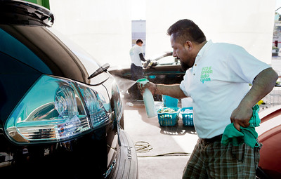 Mario Altimaro sprays a car with the EcoGreen Auto Clean Auto Wash that he is cleaning at EcoGreen Auto Clean, in Redwood City, Calif., on Friday, January 31, 2014.  (LiPo Ching/Bay Area News Group)