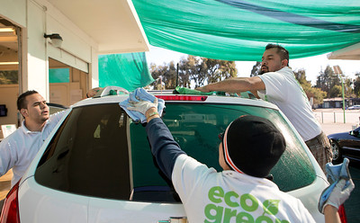 From left, Jose Jiminez, Doris Salguero and Mario Altimaro use microfiber cloths to clean a car after it was sprayed with the EcoGreen Auto Clean Auto Wash at EcoGreen Auto Clean, in Redwood City, Calif., on Friday, January 31, 2014.  (LiPo Ching/Bay Area News Group)