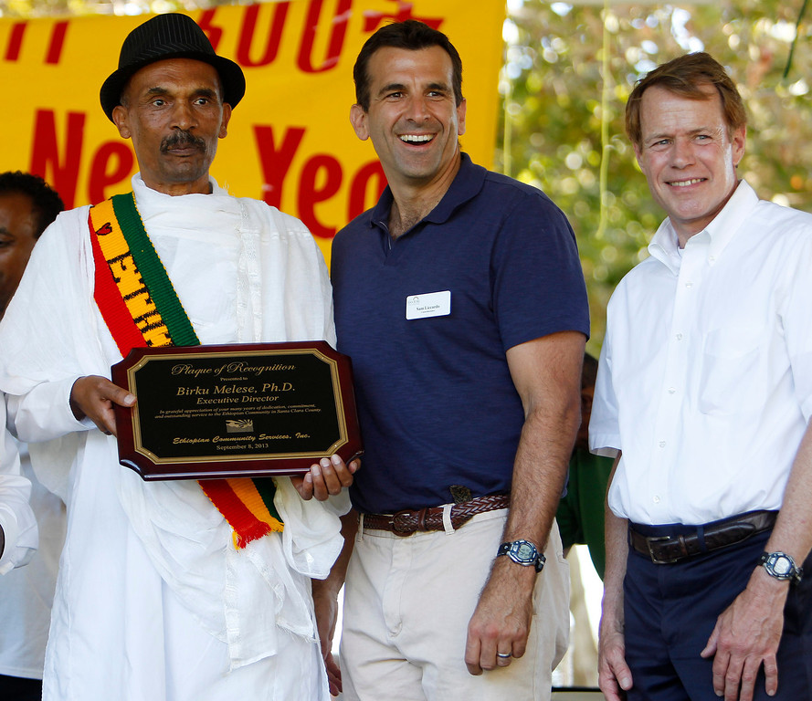 ". Honored with a plaque, first executive director of Ethiopian Community Dr. Birku Melese, left, poses for a picture with San Jose City Councilman Sam Liccardo and Santa Clara County Board of Supervisors, representing District 4 Ken Yeager during the Ethiopian ""Enkutatash\"" new year celebration at Guadalupe River Park Arena Green West in downtown San Jose, Calif.,  on Sunday, Sept. 8, 2013. (Josie Lepe/Bay Area News Group)"