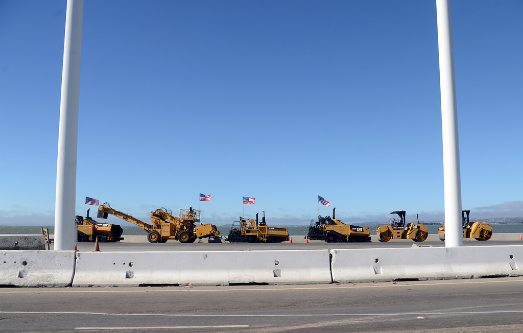 . Flag-bearing construction equipment stages at the foot of the new Bay Bridge in Oakland, Calif., on Wednesday afternoon, Aug. 28, 2013, ready to race to work after the 8 p.m. closure to reconfigure the roadway from the toll plaza to the new Bay Bridge skyway.  (Karl Mondon/Bay Area News Group)