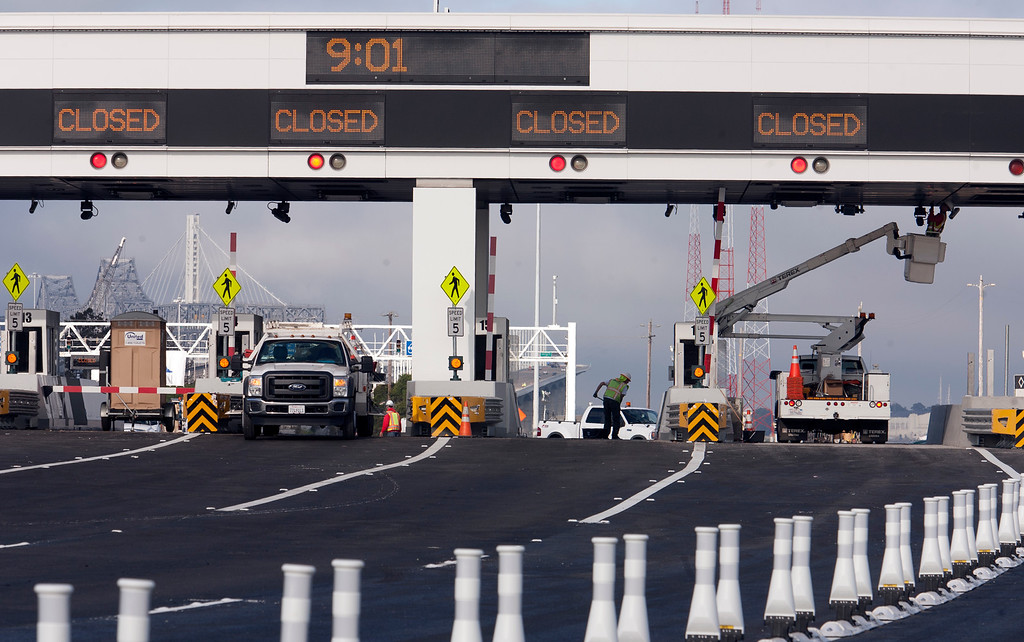 . Caltrans workers ready a new open toll lane for FasTrak patrons at the toll plaza of the Bay Bridge, Sunday, Sept. 1, 2013, in Oakland, Calif., as work continued to prepare the new eastern span of the bridge for its scheduled opening on Tuesday at 5 a.m. (D. Ross Cameron/Bay Area News Group)