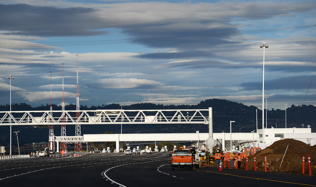 . Crews put the final touches on the Bay Bridge toll plaza as the sun sets Sunday, Sept. 1, 2013 in Oakland, Calif. The bridge\'s announced opening is 5 AM Tuesday. (Karl Mondon/Bay Area News Group)