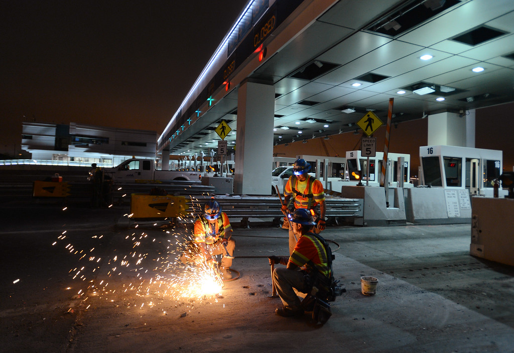 . Anchor bolts are removed from the roadway as lanes 18, 19, and 20 take on a new look without a tool booths to accommodate FasTrak lanes on the Bay Bridge in Oakland, Calif., on Wednesday, Aug. 28, 2013.  (Susan Tripp Pollard/Bay Area News Group)