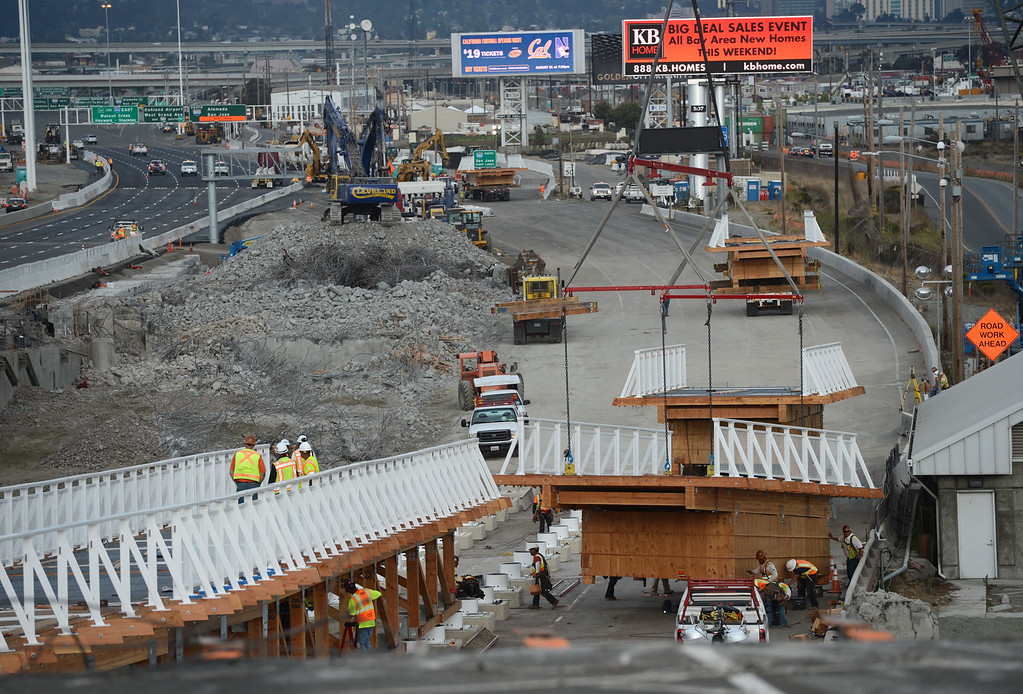 . Crews from MCM Construction work late Sunday afternoon installing the temporary ramp segments that will connect the Bay Bridge Trail to the shoreline in Oakland, Calif. (Karl Mondon/Bay Area News Group)