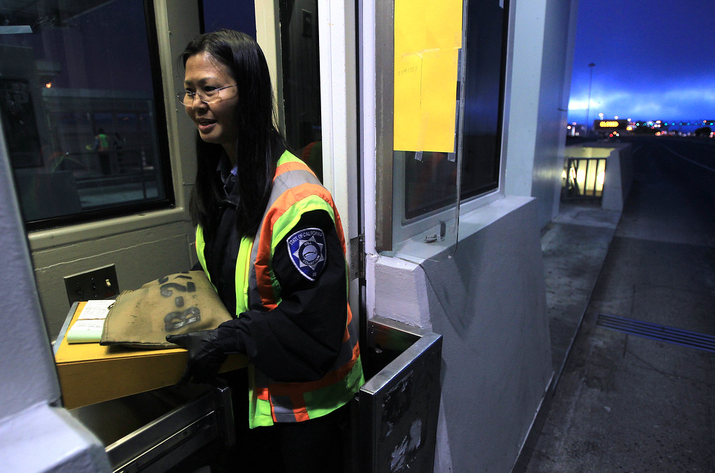 . Toll taker Annabelle Tan, of Hayward, leaves her station after the last car crossed the San Francisco-Oakland Bay Bridge in Oakland, Calif., on Wednesday, Aug. 28, 2013. The old eastern span was shut down permanently at 8 p.m. tonight, and the new span will open to traffic at 5 a.m. on Tuesday, Sept. 3.  Construction of the largest self-anchored suspension bridge in the world began in 2002. (Jane Tyska/Bay Area News Group)