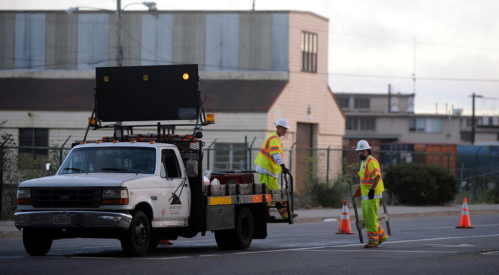 . Workers begin to block off the area near Maritime Street before closing the West Grand Avenue onramp that leads to the Bay Bridge in Oakland, Calif., on Wednesday, Aug. 28, 2013. The bridge is scheduled to reopen on Tuesday, Sept. 3. (Susan Tripp Pollard/Bay Area News Group)