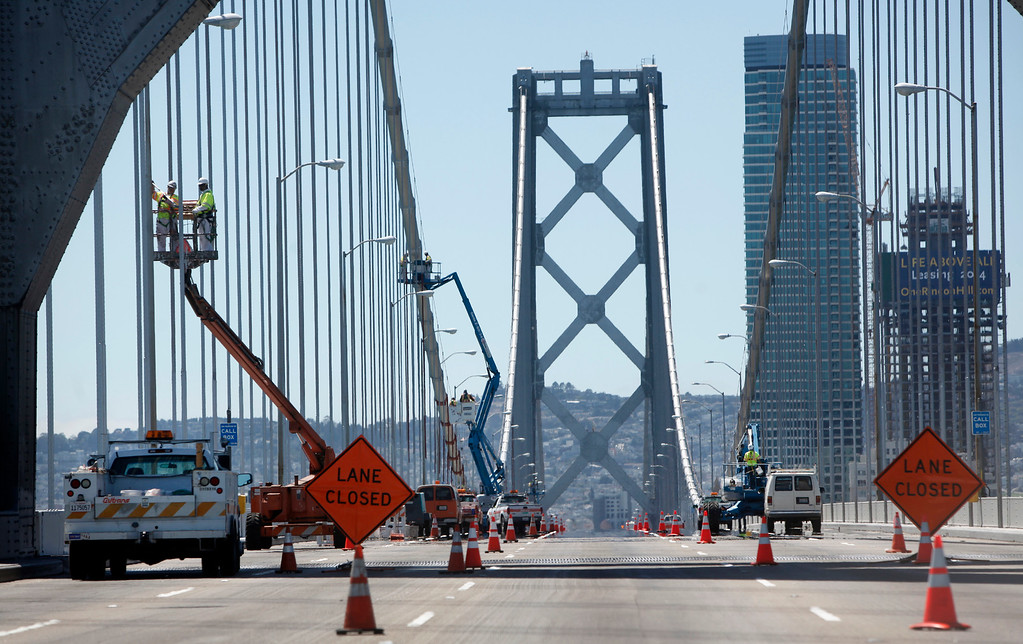 . With the five-day bridge closure in place, maintenance crews work Friday morning, Aug. 30, 2013 painting suspender ropes and fixing the Bay Light\'s installation on the original Bay Bridge\'s western span in San Francisco, Calif. (Karl Mondon/Bay Area News Group)