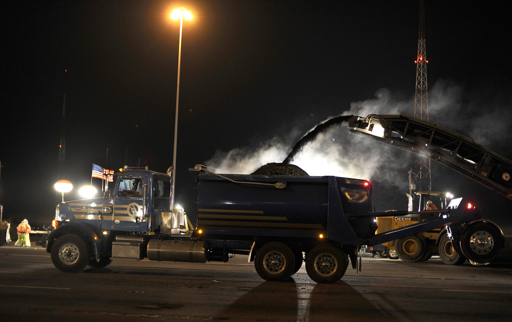 . Steam rises from hot asphalt as work takes place in front of the toll plaza on the Bay Bridge in Oakland, Calif., on Wednesday, Aug. 28, 2013.  (Susan Tripp Pollard/Bay Area News Group)