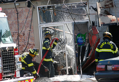 Santa Clara Fire Department firefighters pour water into a restaurant at a five-alarm fire at the Rancho Shopping Center in Santa Clara, Calif., on Wednesday, May 25, 2016. The blaze destroyed several businesses in this strip mall located between Pomeroy Ave. and Lawrence Expressway. (Gary Reyes/Bay Area News Group)