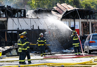 Santa Clara Fire Department firefighters put out hot spots at a five-alarm fire at the Rancho Shopping Center in Santa Clara, Calif., on Wednesday, May 25, 2016. The blaze destroyed several businesses in this strip mall located between Pomeroy Ave. and Lawrence Expressway. (Gary Reyes/Bay Area News Group)