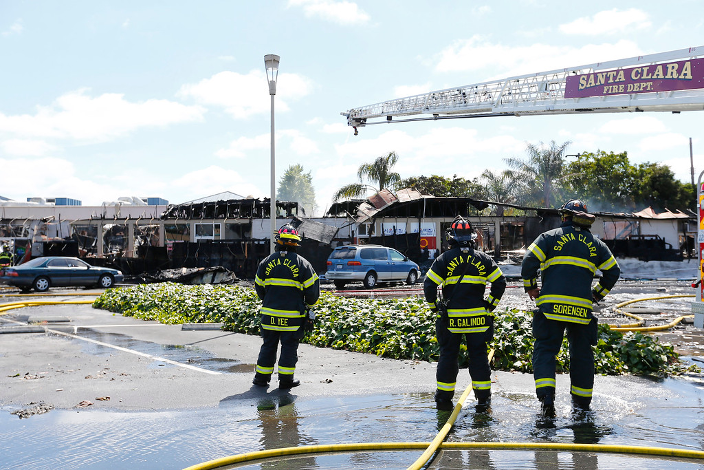 . Santa Clara Fire Department firefighters watch the aftermath of a five-alarm fire at the Rancho Shopping Center in Santa Clara, Calif., on Wednesday, May 25, 2016. The blaze destroyed several businesses in this strip mall located between Pomeroy Ave. and Lawrence Expressway. (Gary Reyes/Bay Area News Group)