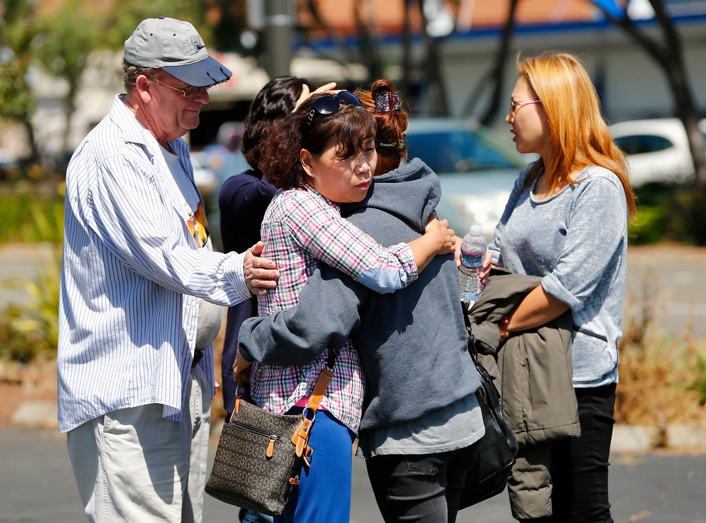 . Yumi Talbot, center, left, comforts Cindy Cho, as they watch the mop up of a five-alarm fire at the Rancho Shopping Center in Santa Clara, Calif., on Wednesday, May 25, 2016. Cho lost her business, Korean Hair Salon, in the blaze. She was in the complex for a year. At far left is Jon Talbot. At far right is friend, Grace Park.The blaze destroyed several businesses in this strip mall located between Pomeroy Ave. and Lawrence Expressway. (Gary Reyes/Bay Area News Group)