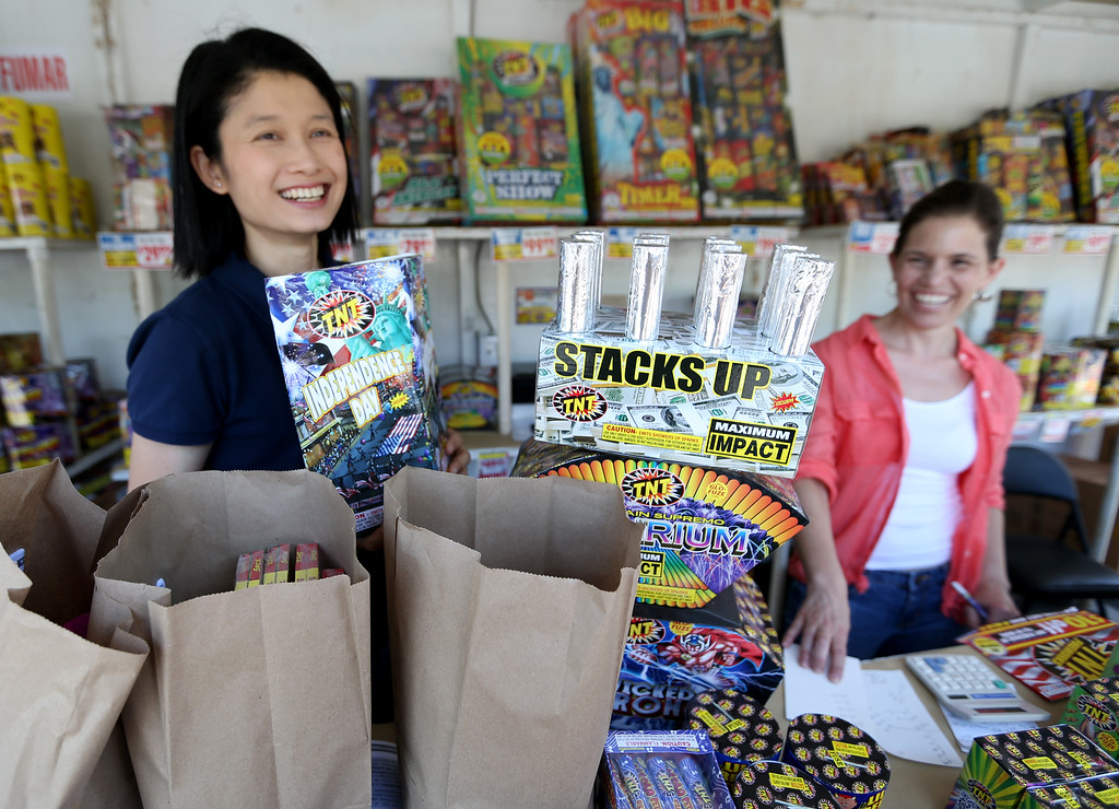 """. Linda Chia, left, and Liz Rathjen pack up \""""safe and sane\"""" fireworks for a customer at a stand along Dublin Boulevard in Dublin, Calif., on Thursday, June 30, 2016.  (Anda Chu/Bay Area News Group)"""