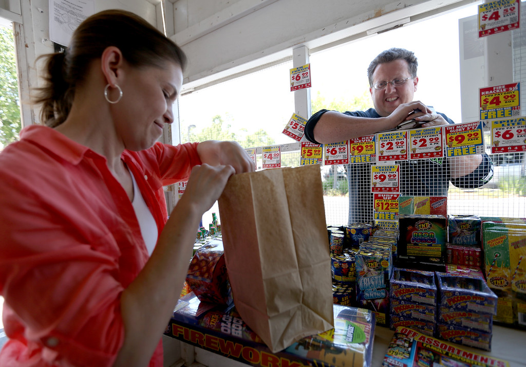 ". Liz Rathjen, left, packs up \""safe and sane\"" fireworks for customer James Bowling, of Livermore, at a stand along Dublin Boulevard in Dublin, Calif., on Thursday, June 30, 2016. (Anda Chu/Bay Area News Group)"