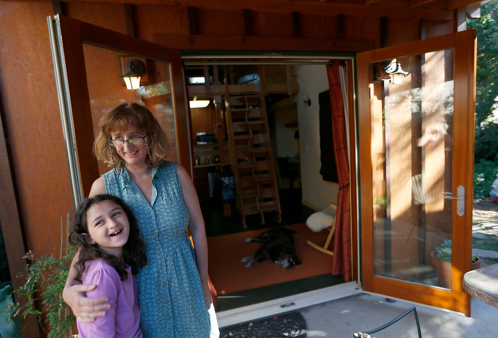 ". Karen Chapple, left, and her daughter Lexi Chapple, 9, are photographed on the porch of  Chapple\'s accessory dwelling unit in the backyard of her home in Berkeley, Calif., on Tuesday, July 12, 2016. Chapple is a UC Berkeley professor and affordable housing expert, and had the tiny 400-square-foot ""granny\"" unit built five years ago. (Jane Tyska/Bay Area News Group)"