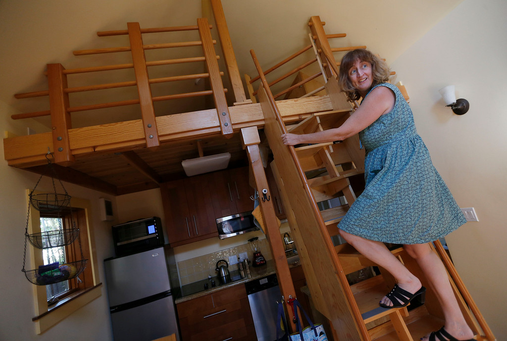 ". Karen Chapple climbs the stairs to the loft in her accessory dwelling unit in the backyard of her home in Berkeley, Calif., on Tuesday, July 12, 2016. Chapple is a UC Berkeley professor and affordable housing expert, and had the tiny 400-square-foot ""granny\"" unit built five years ago. (Jane Tyska/Bay Area News Group)"