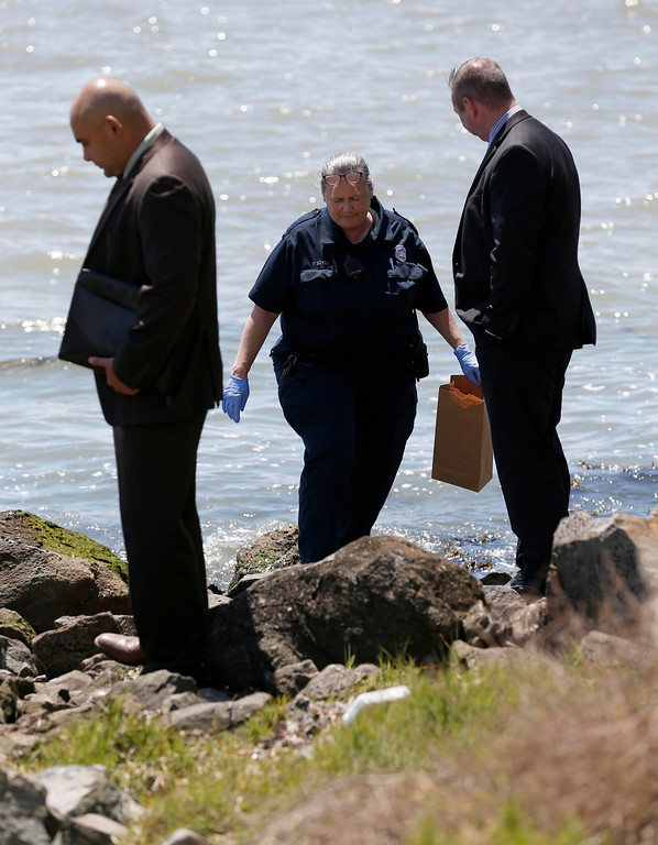 . Oakland police crime scene technician Patricia Boyle, center, and homicide investigators view the scene where a headless and limbless decomposed torso was found on the rocks along Burma Road in West Oakland, Calif., on Wednesday, May 25, 2016.  (Jane Tyska/Bay Area News Group)