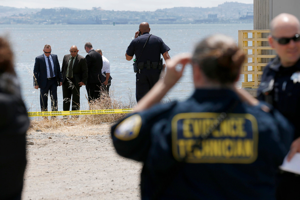 . Oakland police and homicide investigators view the scene where a headless and limbless decomposed torso was found on the rocks along Burma Road in West Oakland, Calif., on Wednesday, May 25, 2016.  (Jane Tyska/Bay Area News Group)