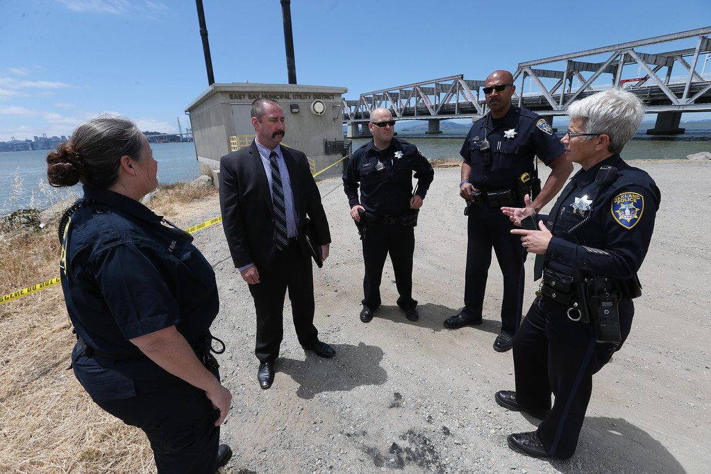 . Oakland police crime scene technician Patricia Boyle, homicide investigator Robert Roche, officers Josh Dement, Sven Hamilton and spokeswoman Johnna Watson, left to right, confer at the scene where a headless and limbless decomposed torso was found on the rocks along Burma Road in West Oakland, Calif., on Wednesday, May 25, 2016.  (Jane Tyska/Bay Area News Group)
