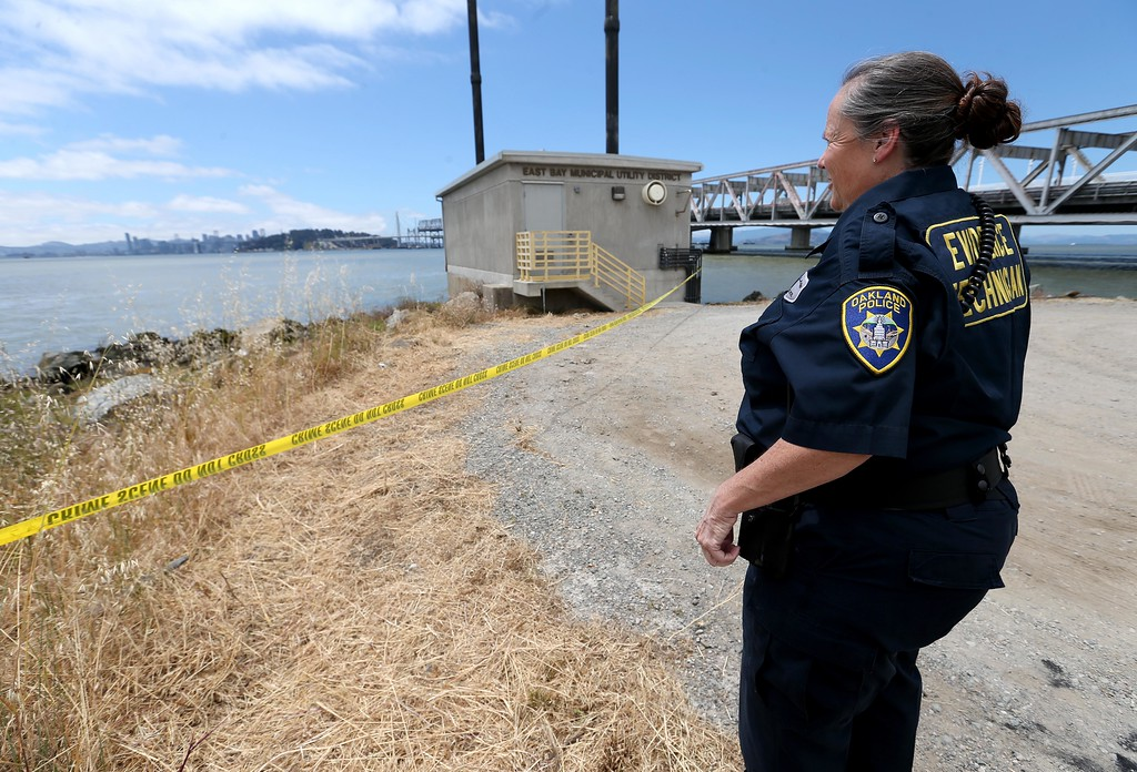 . Oakland police crime scene technician Patricia Boyle surveys the scene where a headless and limbless decomposed torso was found on the rocks along Burma Road in West Oakland, Calif., on Wednesday, May 25, 2016.  (Jane Tyska/Bay Area News Group)
