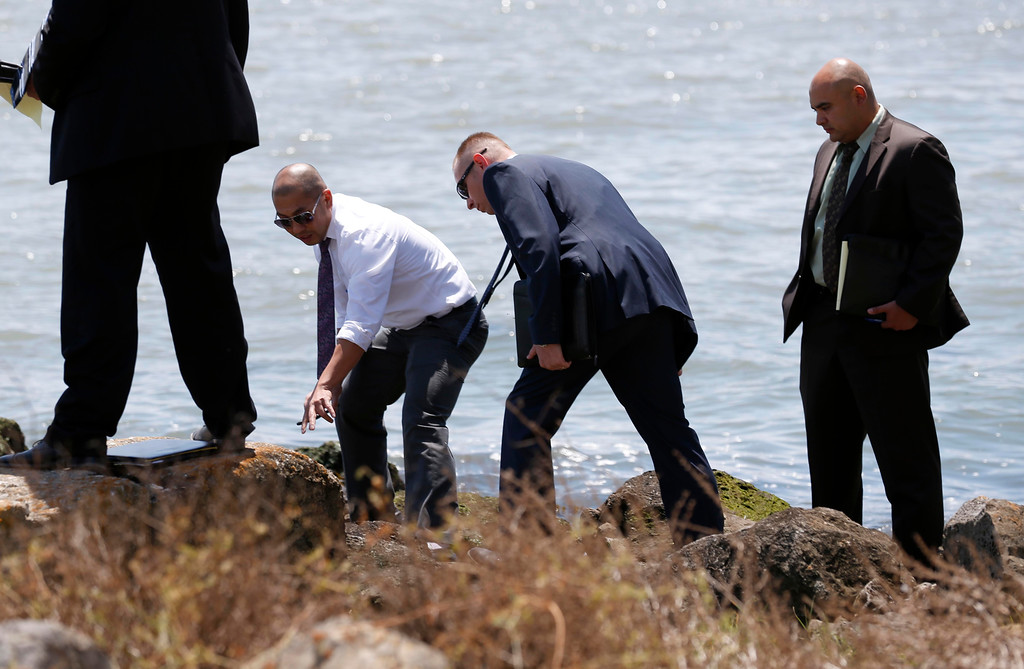. Oakland police homicide investigators view the scene where a headless and limbless decomposed torso was found on the rocks along Burma Road in West Oakland, Calif., on Wednesday, May 25, 2016.  (Jane Tyska/Bay Area News Group)