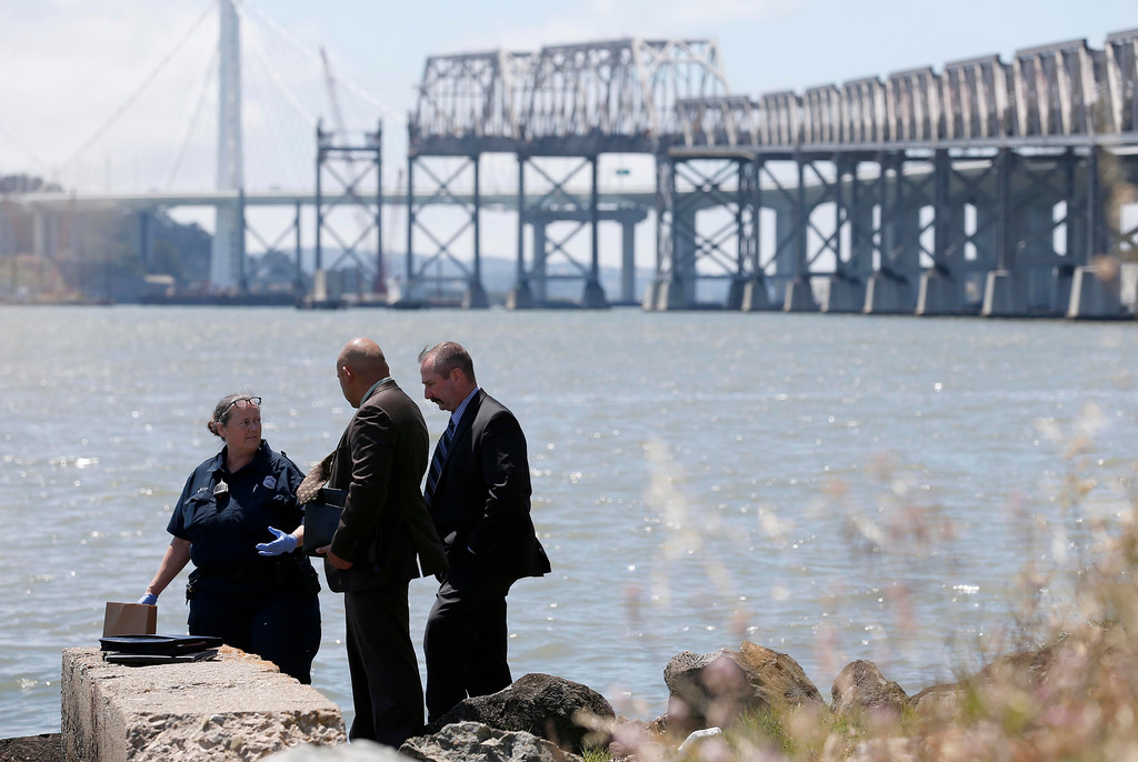 . Oakland police crime scene technician Patricia Boyle, left, and homicide investigators view the scene where a headless and limbless decomposed torso was found on the rocks along Burma Road in West Oakland, Calif., on Wednesday, May 25, 2016.  (Jane Tyska/Bay Area News Group)