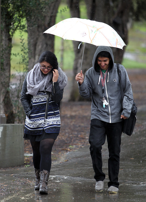 . Susan Wassei and Ankush Kalia, of Fremont, from left, both students at Ohlone College, walk along a path on a rainy day in Fremont, Calif., on Friday, Feb. 28, 2014. Heavy rains fell across parts of the Bay Area causing power outages and minor flooding. (Anda Chu/Bay Area News Group)