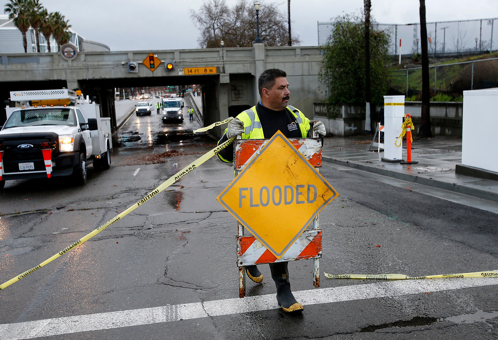 . San Jose city worker Gregory Dominguez moves a sign during the clean up of an underpass on Santa Clara Street near Stockton Avenue that was flooded earlier in the morning in San Jose, Calif. on Friday, Feb. 28, 2014. Heavy rain prompted flooding and wind advisories in the Bay Area. (Gary Reyes/Bay Area News Group)